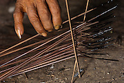 Huaorani Indian, Kempere Tega making Curare tipped darts. Curare is one of the most toxic poisons known to man and is made from a liana. The poison is boiled on the fire. The dart tips are dipped into the poison which hardens into a shiny, lacquer-like coating. They are then ready for the hunt. A small tuft of kapok fluff is plied into a cuff at the blunt end of the dart so as to seal the blowgun airtight. A sharp piranha tooth is used to cut a barb into the dart about 10 cm from the tip so that it will break if the victim tries to remove the dart before the poison takes effect. <br /> Bameno Community. Yasuni National Park.<br /> Amazon rainforest, ECUADOR.  South America<br /> This Indian tribe were basically uncontacted until 1956 when missionaries from the Summer Institute of Linguistics made contact with them. However there are still some groups from the tribe that remain uncontacted.  They are known as the Tagaeri & Taromenane. Traditionally these Indians were very hostile and killed many people who tried to enter into their territory. Their territory is in the Yasuni National Park which is now also being exploited for oil.