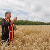 A catholic priest blesses the wheat field during a traditional harvest festival in Opalyi (some 280 kilometers East of capital city Budapest), Hungary on July 13, 2013. ATTILA VOLGYI