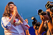 """01 JULY 2011 - BANGKOK, THAILAND:  YINGLUCK SHINAWATRA, leader of the Pheua Thai party, """"wais"""" a traditional Thai greeting to voters at the last Pheua Thai rally of the year in Bangkok Friday. Thailand's divisive election campaign drew to a close Friday in Bangkok. Most of the parties had large rallies in an effort to sway last minute undecided voters. Pheua Thai, the party of ousted Prime Minister Thaksin Shinawatra held a massive rally in Rajamakala Stadium (also called Ramkamhaeng Stadium) to close out their campaign. A monsoon thunderstorm didn't keep people away from the event. Most Thai public opinion polls show Pheua Thai with a healthy lead over their arch rivals (and incumbent party in power) the Democrats. Thaksin's youngest sister, Yingluck Shinawatra, is running for Prime Minister under the Pheua Thai banner. If elected, she will be Thailand's first female Prime Minister.      PHOTO BY JACK KURTZ"""