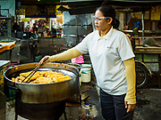 24 AUGUST 2018 - GEORGE TOWN, PENANG, MALAYSIA: A woman makes char kuey, or Chinese fried dough sticks, across the street from Chowrasta Market in central George Town. Chowrasta Market was originally built in 1890 and is the older of two traditional markets in George Town. The original building was torn down and replaced with a modern building in 1961 and has been renovated several times since.     PHOTO BY JACK KURTZ