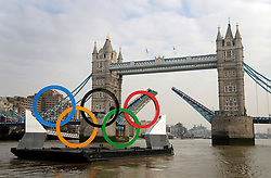 © Licensed to London News Pictures. 28/02/2012, London, UK. Tower Bridge is raised to allow the rings to pass. Giant Olympic rings measuring 11 metres high by 25 metres wide are floated down the River Thames on a barge, marking 150 days to go to the start of the London 2012 Olympic and Paralympic Games. Photo credit : Stephen Simpson/LNP