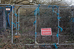 Harefield, UK. 13th February, 2021. Fencing and a sign indicate the closure by contractors working on behalf of HS2 Ltd of a public right of way around the former Hillingdon Outdoor Activities Centre (HOAC) lake. A wildlife protection camp in woodland behind the fencing was occupied by Stop HS2 activists opposed to the high-speed rail link until evicted by bailiffs acting for HS2 Ltd in early 2020.
