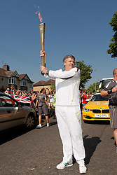 © Licensed to London News Pictures. 23/05/2012. CHIPPENHAM, UNITED KINGDOM. Marathon running fireman Rob Warwick starts the Chippenham stage of the Olympic Torch relay in Wiltshire on Day 4 of the round Britain procession. Photo credit: Mark Chappell/LNP