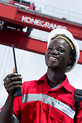 Ship Preparer Sarambo Mamadou supervises the loading of trucks by a KoneCrane RTG crane (background) in Abidjan Container Terminal, Abidjan, Ivory Coast, on November 4, 2010. Photo by Lucas Schifres/Pictobank