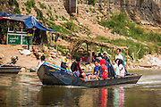 """01 MARCH 2014 - MAE SOT, TAK, THAILAND: Burmese passengers on a boat in the Moie River approach Mae Sot. Boats from Myawaddy, Myanmar (the shore in the background is Myawaddy) drop and pick up passengers for the short trip across the river. Mae Sot, on the Thai-Myanmar (Burma) border, has a very large population of Burmese migrants. Some are refugees who left Myanmar to escape civil unrest and political persecution, others are """"economic refugees"""" who came to Thailand looking for work and better opportunities.    PHOTO BY JACK KURTZ"""