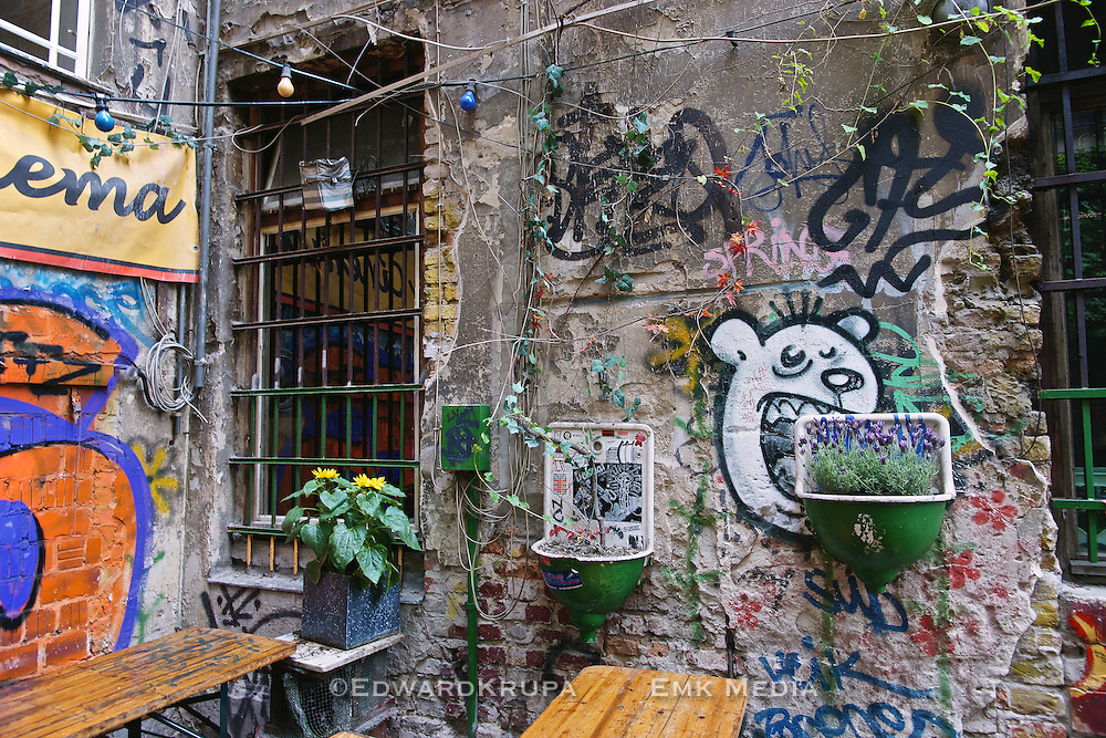 A Berlin outdoor cafe's walls are covered with colourful graffiti and flower planters made of old sinks.