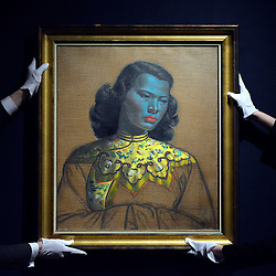 "© Licensed to London News Pictures. 18/03/2013. London, UK A gallery assistant hangs the painting. Press call before the auction of ""Chinese Girl"" by Vladimir Tretchikoff at Bonhams in London today 18th March 2013. The painting is said to be the most widely reproduced and recognisable painting in the world because of its wide reproduction in 1950's art prints. It is expected to fetch 300,000-500,000 GBP at auction on the 20th March. Photo credit : Stephen Simpson/LNP"