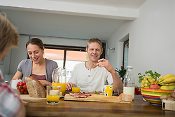 Young family sitting eating healthy breakfast