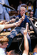 President Jimmy Carter - on vacation in his hometown of Plains, Georgia - holds a very informal news conference while sitting on the freight platform of the old Plains railway depot. - To license this image, click on the shopping cart below -