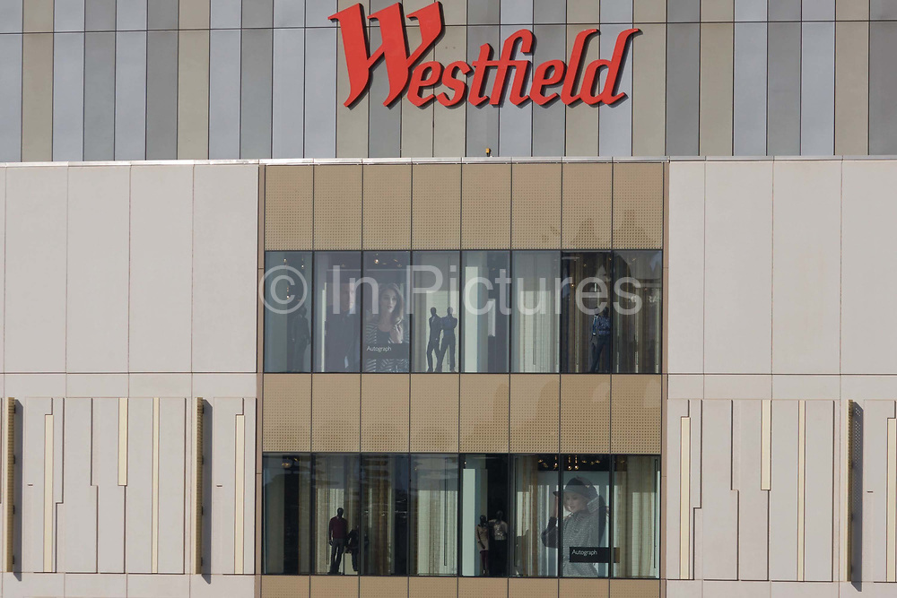 Architecture and design of the Westfield City shopping centre in Stratford, home of the 2012 Olympics. In the windows we see mannequins and models wearing the latest styles of this high-street retailer. Situated on the fringe of the 2012 Olympic park, Westfield hosted its first day to thousands of shoppers eager to see Europe's largest urban shopping centre. The £1.45bn complex houses more than 300 shops, 70 restaurants, a 14-screen cinema, three hotels, a bowling alley and the UK's largest casino. It will provide the main access to the Olympic park for the 2012 Games and a central 'street' will give 75% of Olympic visitors access to the main stadium so retail space and so far 95% of the centre has been let. It is claimed that up to 8,500 permanent jobs will be created by the retail sector.