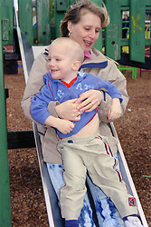 Single mother sliding down slide in playground with young son,