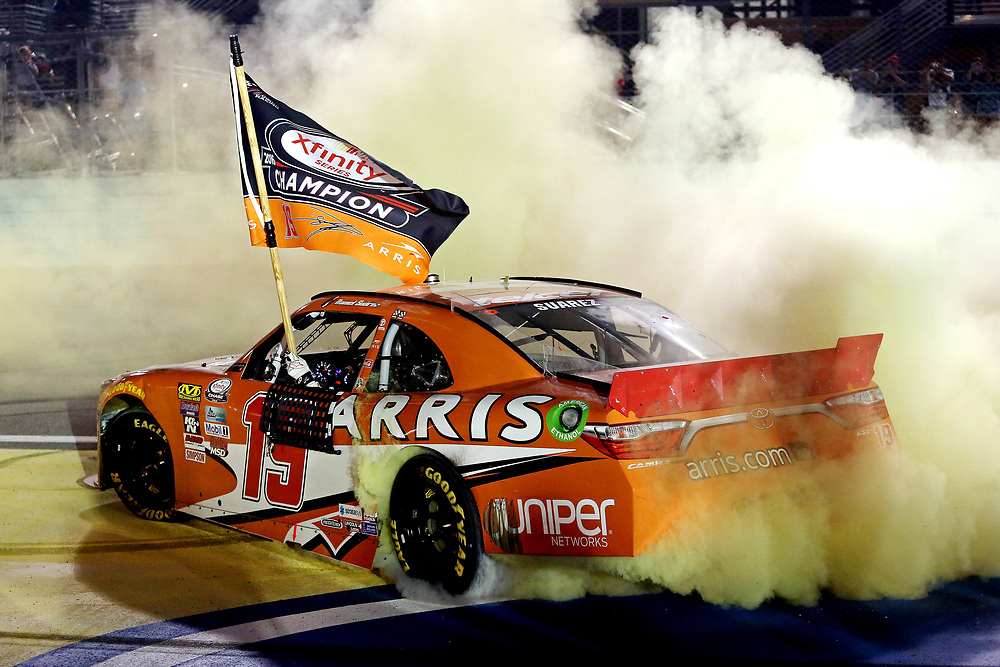 Nov 19, 2016; Homestead, FL, USA; NASCAR Xfinity Series driver Daniel Suarez (19) celebrates winning the NASCAR Xfinity Series championships after the Ford Ecoboost 300 at Homestead-Miami Speedway. Mandatory Credit: Peter Casey-USA TODAY Sports