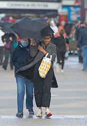 © Licensed to London News Pictures. 02/11/2020.  <br /> Bromley, UK. Two shoppers holding onto their umbrella in the wind and the rain. After the second lockdown announcement by Prime Minister Boris Johnson at the weekend the number of Christmas shopping days has been halved. Shoppers flock to Bromley High Street in South East London today to by gifts. Photo credit:Grant Falvey/LNP