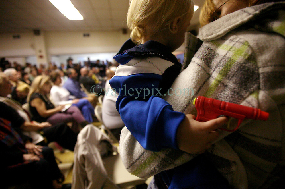 26 Jan 2012. New Orleans, Louisiana USA. .A young boy holds a toy gun at a community meeting held at a school on the same block of an attempted carjacking turned homicide. Residents gathered to grill NOPD Chief Ronal Serpas and elected officials. Yesterday local good samaritan Harry 'Mike' Ainsworth was shot and killed as he attempted to foil a carjacking outside the school at 7.00am. His children, aged 9 & 11 sobbed as he died in their arms..Photo; Charlie Varley