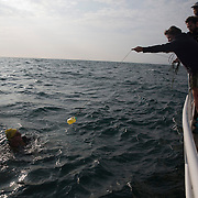 Triathlete Paul Parrish is passed liquid food in a plastic carton as he undertakes the swim section of his Arch to Arch triathlon attempt in the Channel between England and France September 15, 2014.