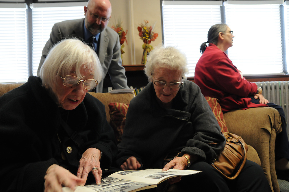 Former St. Eulalia parishioners Therese Killgallon Smrstik (L) and her sister Nancy Killgallon Ziegler reminisce over a parish yearbook with Therese's son Bob Smrstik (rear) in the newly- inaugurated Quinn Community Center in Maywood.