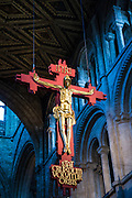 A crucifix hanging from ceiling inside Peterborough cathedral, one of the finest Norman cathedrals in England. Founded as a monastic community in 654 AD, it became one of the most significant medieval abbeys in the country, the burial place of two queens and the scene of Civil War. Peterborough, Cambridgeshire. UK
