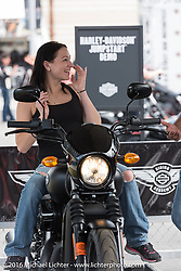 "Melinda Fox of Palm Coast, FL with Harley-Davidson's Dane Lauber in the ""Jumpstart"" display of the Harley-Davidson area at Daytona International Speedway during the Daytona Bike Week 75th Anniversary event. FL, USA. Saturday March 5, 2016.  Photography ©2016 Michael Lichter."