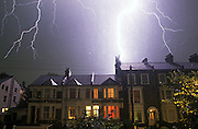 A lightning bolt spreads across night skies over South London terraced homes. .Lightning is an atmospheric discharge of electricity accompanied by thunder, which typically occurs during thunderstorms, and sometimes during volcanic eruptions or dust storms. In the atmospheric electrical discharge, a leader of a bolt of lightning can travel at speeds of 220,000 km/h (140,000 mph), and can reach temperatures approaching 30,000 °C (54,000 °F), hot enough to fuse silica sand into glass channels known as fulgurites which are normally hollow and can extend some distance into the ground. There are some 16 million lightning storms in the world every year.