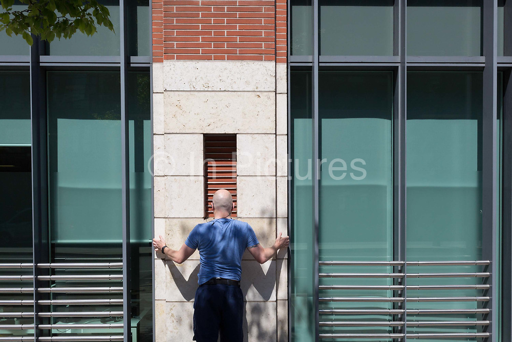 Having completed his urban run through the City of London the capitals financial capital, an office worker stretches against the exterior wall of his place of work, on 13th May, in London, England.