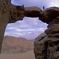 A trekker hikes across a huge stone arch on Jebel (Mount) Burdah in Jordan's Wadi Rum, near the edge of the Arabian Desert.