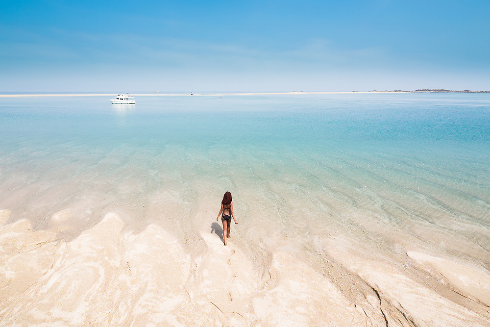 Person walking out into the crystal clear calm turquoise waters at the Minquiers, Jersey with boats and sand banks beyond