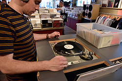 © Licensed to London News Pictures. 21/04/2018. LONDON, UK.  An analogue music fan listens to a record inside an independent record shop in Soho on the 11th annual Record Store Day.  Over 200 independent record shops all across the UK come together to celebrate the unique culture of vinyl music with special releases made exclusively for the day.  Photo credit: Stephen Chung/LNP