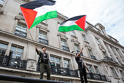 London, UK. 26th June, 2021. Pro-Palestinian activists wave flags from the top of a bus shelter during the United Against The Tories national demonstration organised by the People's Assembly Against Austerity in protest against the policies of Prime Minister Boris Johnson's Conservative government. The demonstration contained blocs from organisations and groups including Palestine Solidarity Campaign, Stand Up To Racism, Stop The War Coalition, Extinction Rebellion, Kill The Bill and Black Lives Matter as well as from trade unions Unite and the CWU.