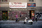 A man walks his dogs past students protesting gentrification in Naples, Italy. The city, long dilapidated now has areas that are expensive for locals, wary of the growing number of tourists and property speculators.