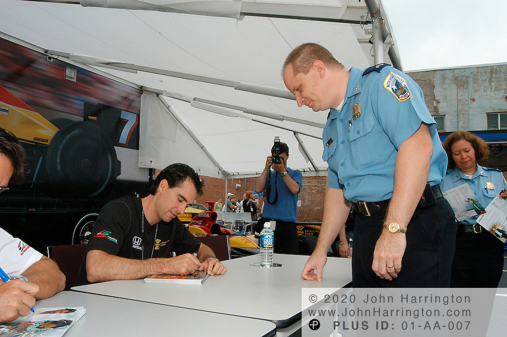 Mario Andretti and Brian Herta, two members of Andretti Green Racing, chat with a member of their racing team at an XM event on Wednesday June 23, 2004.