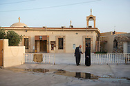 Abuna Dnha Toma (right) is the priest at Santa Maria Harmota, a Chaldean Catholic church with 170 families on the outskirts of Koya, Iraq, In this image he talks with a parishioner outside the church. The priest studied in Baghdad and also for four years in Beirut.