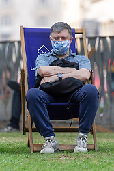 © Licensed to London News Pictures. 19/07/2021. London, UK. A man wearing a face mask relaxes in a deck chair in Leicester Square on Freedom Day marking the final government Covid 19 lifting of restrictions. Photo credit: Ray Tang/LNP