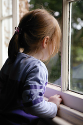 Young girl alone; looking out of a window,