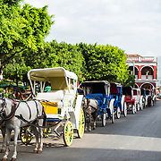 Horse drawn carriages line up along the western side of Parque Central to take tourists on sightseeing tours of the historic heart of Granada. Parque Central is the main square and the historic heart of Granada, Nicaragua.