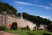 Terraced mill workers' homes at New Lanark, the industrial revolution community village managed by social pioneer Robert Owen. New Lanark is on the River Clyde, approximately 1.4 miles (2.2 kilometres) from Lanark, in South Lanarkshire, Scotland. It was founded in 1786 by David Dale, who built cotton mills  and housing for the mill workers. Dale built the mills there to take advantage of the water power provided by the river. Under the ownership of a partnership that included Dale's son-in-law, Robert Owen, a Welsh philanthropist and social reformer, New Lanark became a successful business and an epitome of utopian socialism. The New Lanark mills operated until 1968 and is now one of five UNESCO World Heritage Sites in Scotland.