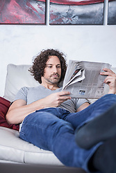 Man lying down on couch and reading a newspaper, Munich, Bavaria, Germany