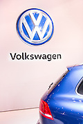 New York, NY, USA-23 March 2016. Volkswagen's VW logo, seen on a display wall at the New York International Auto Show behind a Touareg. VW had only 12 production vehicles and a concept car at the show, and no diesel cars.