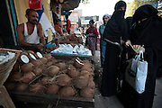 Two women buy some coconuts from a street vendor.  The slum of Cheetah Camp on the outskirts of Mumbai, India is a predominantly muslim community on living on the fringe while the city continues to grow.
