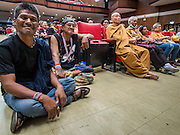 14 DECEMBER 2013 - BANGKOK, THAILAND: Spectators at an anti-government reform forum at Thamassat University in Bangkok, sit on the floor in an aisle during the forum. The Thai anti-government movement, called the People's Democratic Reform Committee (PRDC) sponsored a forum Saturday to establish guidelines for political reform in Thailand. The opposition leader, Suther Thaugsuban, said his movement will not participate in a similar forum, sponsored by the government scheduled for Sunday. Thailand's political impasse continues with the opposition calling for the caretaker government of Prime Minister Yingluck Shinawatra to step down. Yingluck has, so far, refused to step down from her caretaker roll. Crowds at the anti-government rallies have shrunk substantially since the collapse of the government earlier in the week.        PHOTO BY JACK KURTZ