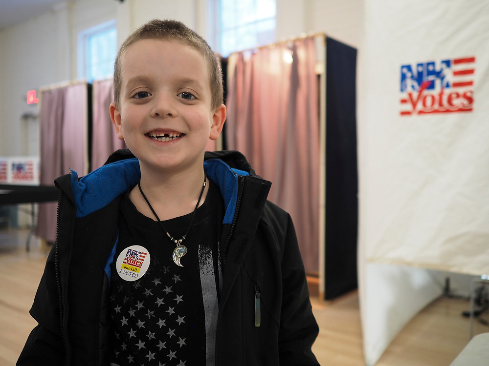 """A young boy in Nelson, New Hampshire wears both a huge grin and an """"I voted"""" sticker."""