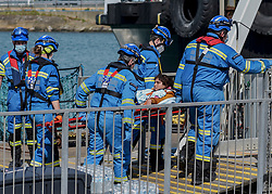 © Licensed to London News Pictures. 12/08/2021. Dover, UK. A migrant is carried on a stretcher by members of the Coastguard Search & Rescue team as she arrives ashore from a Border Force vessel at Dover Harbour in Kent after crossing the English Channel today. Hundreds of migrants have made the crossing in recent weeks. Photo credit: Stuart Brock/LNP