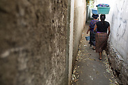 Abuelita and Silva walk down a narrow pathway to access Lake Atitlan where the family washes their laundry.
