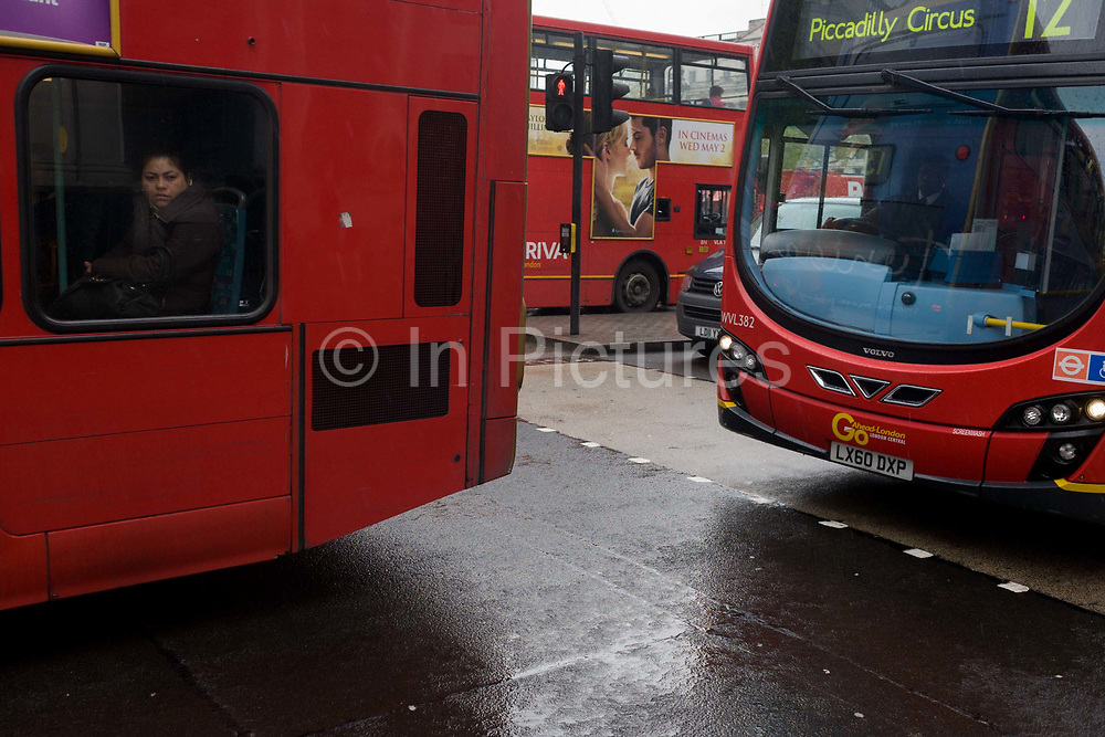 A London bus passenger shows the everyday tedium of commuting in the UK capital. The woman looks bored and depressed as she stares out from her rear seat. Behind the vehicle we see a romantic film ad that seems to contrast the woman's solitary existence. Rain has recently fallen on the capital's streets making the day seem more mundane.