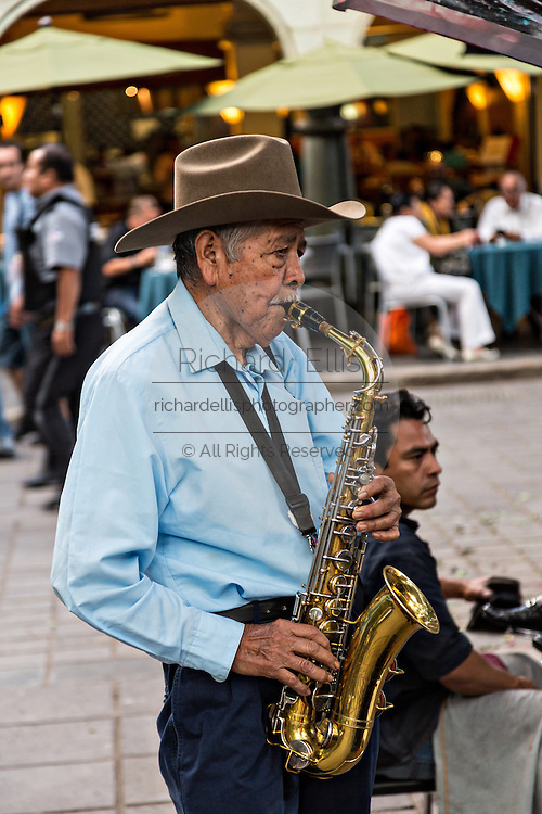 An elderly musician plays the saxophone in the Zocalo  in Oaxaca, Mexico.