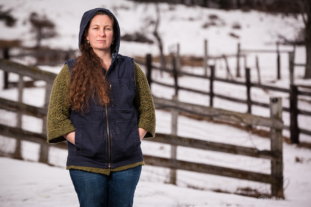 A portrait of a farmer in front of split rail fences and snow-covered fields.