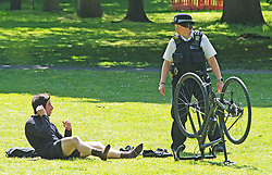 ©Licensed to London News Pictures 06/05/2020  <br /> Greenwich, UK. A police officer on patrol asking this cyclist to stop sunbathing and move on. People out and about in Greenwich park, Greenwich, London exercising and enjoying the warm sunny weather.  Photo credit:Grant Falvey/LNP