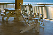 Tables and chairs on a terrace overlooking the beach