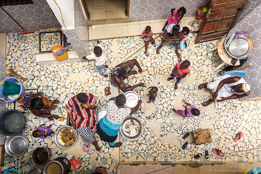 August 12, 2015. Wrestler Kherou Ngor (middle, playing with child) eats lunch with his uncle's big family, who is a very respected Marabout, as shamans, wizards and clergymen are called in Senegal. Witchcraft plays a big part in the Senegalese wrestling.