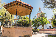 The bandstand and dome of the Parroquia de San Pedro Apóstol church or Saint Paul the Apostle provincial church from the Jardín Principal in Mineral de Pozos, Guanajuato, Mexico. The town, once a major silver mining center was abandoned and left to ruin but has slowly comeback to life as a bohemian arts community.