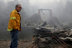 November 10, 2018 - Chico, California, U.S. - The iconic 132-year-old Honey Run Bridge sits in ruins on Butte Creek east of Chico on Saturday. David Little, a fourth generation Chico native and editor of the local Chico Enterprise-Record, surveys the ruins of the famous covered bridge, another victim of the deadly Camp fire. (Credit Image: © Karl Mondon/East Bay Times/TNS via ZUMA Wire)